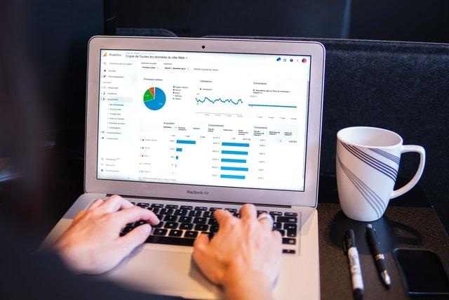 Devenir nomade digital grâce à un e-commerce. Personne qui regarde les statistique de son e-commerce sur son ordinateur portable.