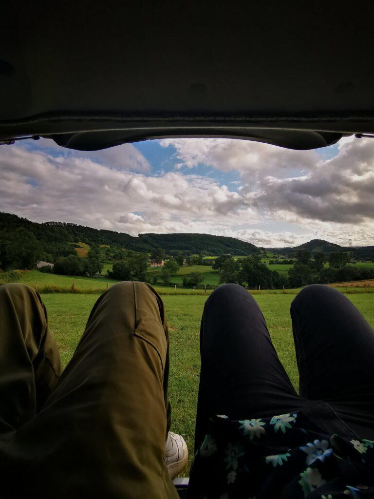 nos jambes et en arrière plan la vue de notre spot pour la nuit lors de notre road trip d'un mois en France